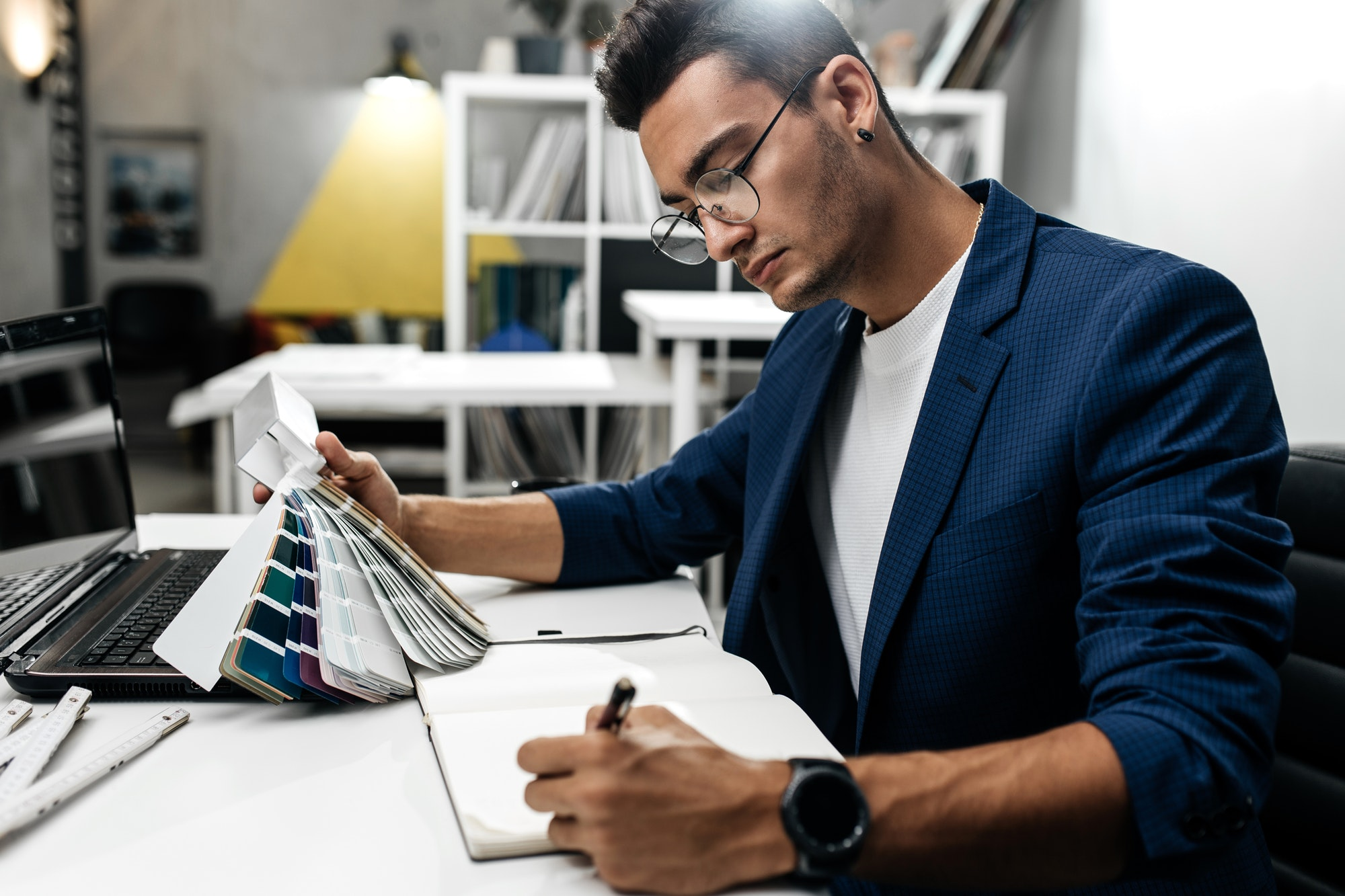 The architect in glasses and in a blue jacket is working with catalog of colors on the desk in the